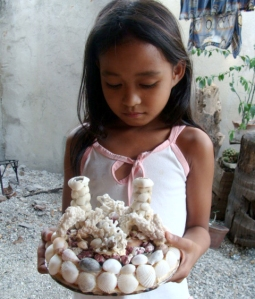A young lady holding a shell craft from San Esteban, Ilocos Sur.