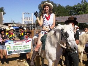 What a beautiful girl riding a white horse. She is one of the muses of the rodeos.